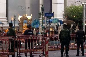 Police and soldiers stand next to the damaged religious shrine in central Bangkok late on Aug 18, 2015.