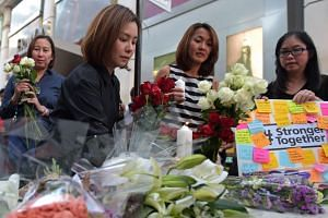 Thai office workers lay flowers for victims killed in a bomb blast outside a religious shrine in Bangkok on Aug 18, 2015.