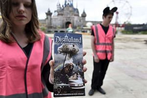 A performer holding a Dismaland brochure
