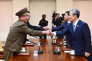 North Korean officials (left) meet their counterparts from South Korea for talks seeking a way out of an escalating crisis that has pushed their militaries to the brink of armed conflict.