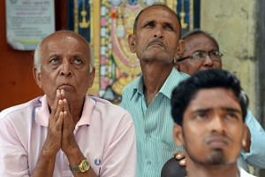 Onlookers watch share prices on a screen outside the Bombay Stock Exchange in Mumbai on Aug 24, 2015.