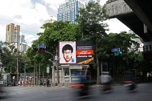Vehicles pass by a digital billboard showing the sketch of a man suspected to be the Bangkok bomber in central Bangkok on Aug 22, 2015.