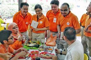 National Solidarity Party member  Mohamed Fazli Talip (second right) during a walkabout in Tampines East on Aug 15, 2015.