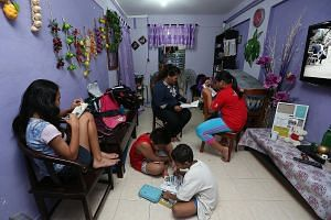 Madam Nor and her children in the living room of their two-room rental unit in Ang Mo Kio. She hopes to get her own flat again with the help of the Fresh Start Housing Scheme.