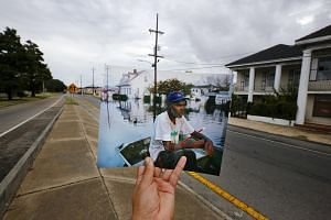 Photographer Carlos Barria holds a print of a photograph he took in 2005, as he matches it up at the same location 10 years on, in New Orleans, United States on Aug 16, 2015.