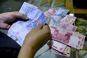 A customer counts out Indonesian rupiah banknotes at a shop in Jakarta on Aug 25, 2015.