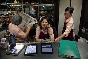 Ms Woon Ai Chun, 61, who has worked at the Shashlik restaurant for 11 years, prepares one of the restaurant's signature desserts, the Cherry Jubilee. Ms Jean Jee, 58, catches up on the news while Ms Wee Mui Quee (at right), 56, keeps herself busy as