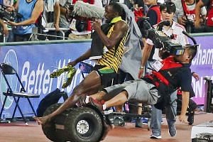 Usain Bolt of Jamaica is hit by a cameraman on a Segway as he celebrates winning the men's 200m final at the 15th IAAF World Championships in Beijing, China.