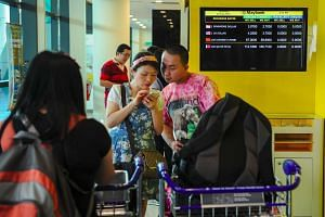 Travellers using their smartphone next to a money changer at the Kuala Lumpur International Airport 2 (KLIA 2) in Sepang on Aug 20, 2015.