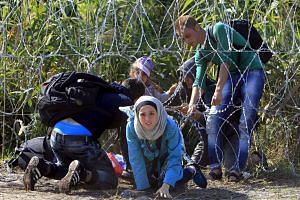 A Syrian migrant family enters Hungary at the border with Serbia near Roszke.