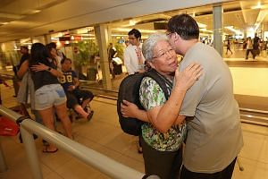 Ms Betty Ong, who was hurt in the bomb attack at the Erawan Shrine on Aug 17, receiving a hug from a relative at the airport last night.