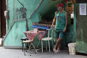 A stall-holder waits for customers at a food stand in Rio de Janeiro, Brazil. Unemployment in the country is at 7.5 per cent and rising and the national currency is down about 25 per cent this year against the US dollar.