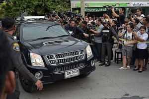 Police make way for a car - part of a convoy carrying a suspect in the Aug 17 Bangkok shrine bombing.