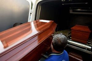 Men carry load a funeral vehicle the coffins of migrants and three-year old Aylan Kurdi, a Syrian boy whose body was washed up on a Turkish beach after a boat carrying refugees sank as it crossed to the Greek island of Kos, at the morgue in Mugla, so
