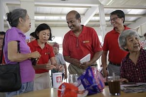 Prof Paul Tambyah (centre) chats with residents at the Empress Road food centre as Mr Sidek Mallek looks on. Both men are Singapore Democratic Party candidates for Holland-Bukit Timah GRC.