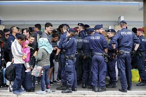 Migrants stand next to police on a platform after arriving at a railway station in Vienna, Austria, on Sept 5, 2015. Austria and Germany threw open their borders to thousands of exhausted migrants on Saturday.