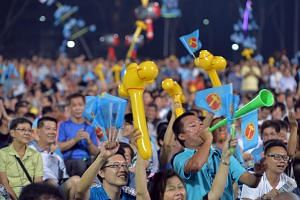 A supporter blows his vuvuzela as others wave yellow inflateable hammers at the Workers' Party's (WP) rally for Nee Soon GRC at Yishun Stadium on Sept 4, 2015.