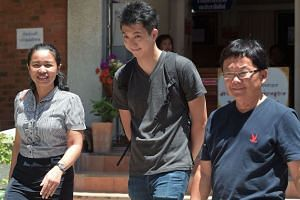Hong Kong photojournalist Anthony Kwan Hok-chun (centre) walks with lawyers as they arrive at Samutprakarn provincial court on Sept 7, 2015.