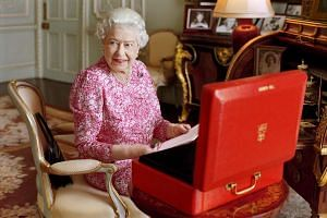 Britain's Queen Elizabeth sits in her private audience room in Buckingham Palace next to one of her official red boxes in which she receives documents and papers from government officials.
