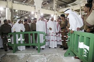 Saudi officials stand near damage caused by a collapsed crane at the Grand Mosque in the Muslim holy city of Mecca, Saudi Arabia on Sept 11, 2015.