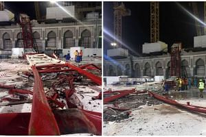 Saudi emergency teams stand next to a construction crane after it crashed into the Grand Mosque of Saudi Arabia's holy Muslim city of Mecca on Sept 11, 2015.