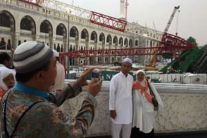 Muslim pilgrims take pictures in front of the crane that collapsed the day before at the Grand Mosque on Sept 12, 2015.