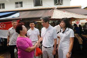 Mr Lim Swee Say (second from right) and his East Coast GRC teammates Jessica Tan and Lee Yi Shyan thanking residents on a tour of the constituency yesterday.
