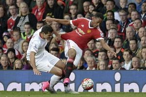 Martial (right) is tackled by Liverpool's Croatian defender Dejan Lovren during the match.