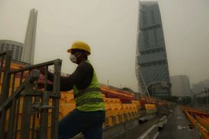A foreign worker wearing a mask while working at the Stamford Grandstand along Nicoll highway at about 5pm on Monday, Sept 14, 2015.