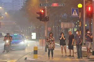 Hazy conditions causing discomfort to pedestrians near Rivervale Plaza at about 7pm yesterday. At 9pm yesterday, the 24-hour PSI was between 133 and 166.