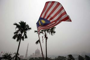 A Malaysian flag flutters in front of the Putra Mosque shrouded in haze in Putrajaya, Malaysia, on Sept 14, 2015.