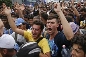 Migrants shout to open the border near the village of Horgos, Serbia, Sept 15, 2015.