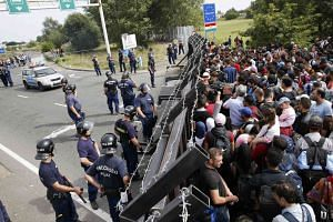 Migrants stand in front of a barrier at the border with Hungary near the village of Horgos, Serbia, Sept 15, 2015.