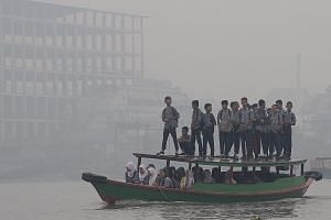 Indonesian students crossing the Ogan River on a wooden boat in the haze as they head to their school in Palembang, South Sumatra, yesterday.