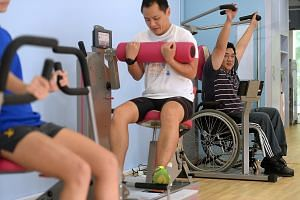 Mr Colin Loh (in wheelchair) trying out the new iFit inclusive gym. The fitness centre has features such as machines with removable seats for wheelchair users, and Braille dots (below) on its treadmill user panels.