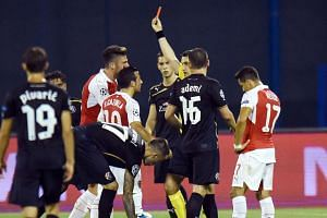 The referee shows red card to Arsenal's midfielder Oliver Giroud (right).