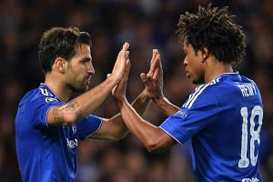 Chelsea midfielder Cesc Fabregas (left) celebrates with striker Loic Remy after scoring his team's fourth goal.