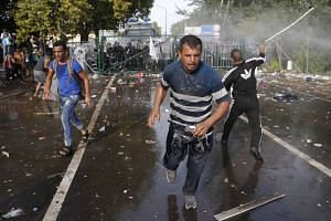 Migrants run as Hungarian riot police fire tear gas and water cannon at the border crossing with Serbia.