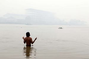 A man prays as he bathes in the Ogan River amid haze in Palembang, South Sumatra, Indonesia on Sept 16, 2015