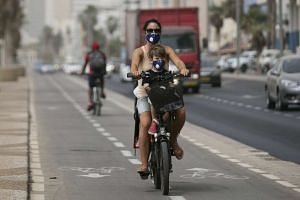 A woman and child wear masks as they ride in traffic in Israel.