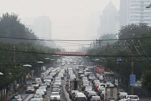 Cars drive along a street on a polluted day in Beijing on July 24, 2015.
