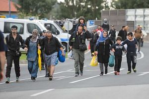 Slovenian police take a group of migrants and refugees from the Rigonce-Harmica border crossing to a registration centre.