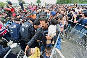 Thousands of migrants wait for their departure to Germany at the Austrian side of the Hungarian-Austrian border.