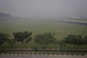 A cyclist travels along Sengkang East Road with HDB blocks on the horizon barely visible in hazy conditions on Sept 24, 2015, at 9.20am.