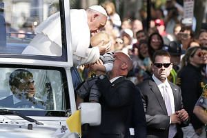 Pope Francis kisses a child during a parade in Washington, DC.