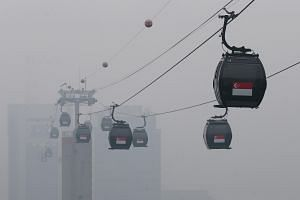 Cable cars shrouded in smog at Mount Faber, Singapore.