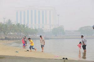 Parents and children enjoying a dip by the sea at Stulang, Johor Baru during the Hari Raya Aidiladha and school holiday break despite the haze on Sept 24, 2015.