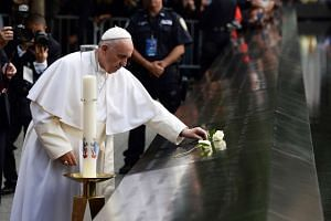 Pope Francis places a white rose on the names of the September 11 victims at the edge of the South Pool of the 9/11 memorial in New York.