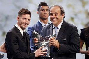 Michel Platini (right) presents Barcelona's Lionel Messi with the Best Player UEFA 2015 Award as Cristiano Ronaldo looks on.