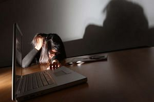 Posed photo of a person crouching in a corner in desolation to illustrate a story on bullying.